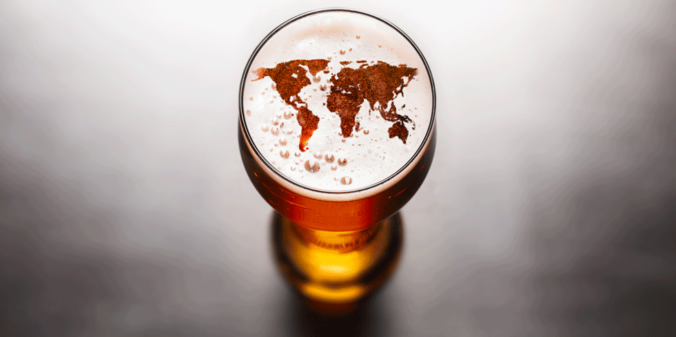Beer glass with world map in foam